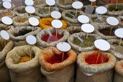 Chiuda sulle borse delle spezie con i prezzi da pagare in bianco immagini stock