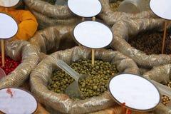 Chiuda sulle borse delle spezie con i prezzi da pagare in bianco fotografie stock
