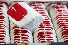 Chiuda sulle bustine di tè con le etichette rosse in scatola Immagini Stock