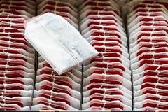 Chiuda sulle bustine di tè con le etichette rosse in scatola Fotografie Stock Libere da Diritti