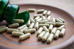 Chiuda sulle capsule dell'estratto del tè verde ed imbottigli su un marrone p dell'argilla Fotografia Stock