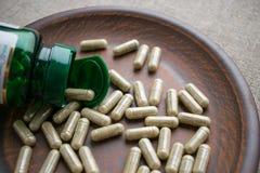Chiuda sulle capsule della biotina ed imbottigli sulla piastrina di marrone dell'argilla sul burla Immagini Stock