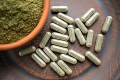 Chiuda sulle capsule e sulla polvere verdi su un piatto di marrone dell'argilla su un Bu immagine stock libera da diritti