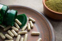 Chiuda sulle capsule, sulla bottiglia e sulla polvere verdi su un piatto di marrone dell'argilla Fotografia Stock