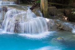Chiuda sulle cascate blu della corrente in foresta profonda Immagine Stock