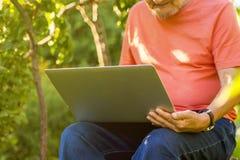 Chiuda sulle free lance pensionate anziano di seduta che lavorano al computer portatile su una stazione turistica estiva immagine stock libera da diritti