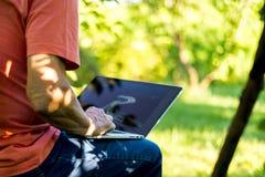 Chiuda sulle free lance pensionate anziano di seduta che lavorano al computer portatile su una stazione turistica estiva fotografia stock