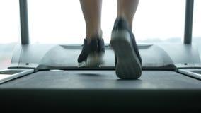 Chiuda sulle gambe del ` s della donna su una pedana mobile nella palestra archivi video