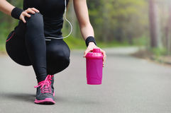 Chiuda sulle gambe della donna sportiva di stile di vita sano con la cuffia a Fotografia Stock Libera da Diritti