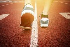 Chiuda sulle giovani gambe della donna di forma fisica che corrono sulla traccia della spiaggia dell'alba Fotografia Stock