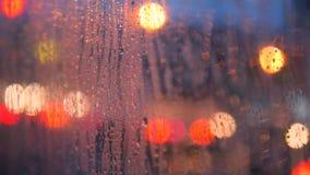 Chiuda sulle gocce di pioggia sul vetro di finestra dell'automobile con le luci vaghe Bokeh dell'automobile della città di notte  video d archivio