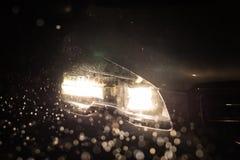 Chiuda sulle luci dell'automobile alla notte Tempo piovoso Fotografie Stock