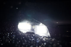 Chiuda sulle luci dell'automobile alla notte Tempo piovoso Immagine Stock Libera da Diritti
