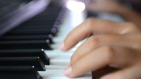 Chiuda sulle mani basse di profondità di campo del colpo della donna che giocano la stampa della tastiera di piano sulla chiave i video d archivio