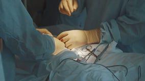 Chiuda sulle mani che indossano i guanti chirurgici che fanno funzionare il gruppo video d archivio