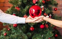 Chiuda sulle mani che tengono la palla di Natale sul fondo dell'albero di natale Fotografie Stock