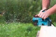 Chiuda sulle mani del carpentiere che funzionano con la piallatrice elettrica sulla plancia di legno fotografia stock