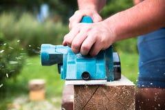 Chiuda sulle mani del carpentiere che funzionano con la piallatrice elettrica sulla plancia di legno immagine stock