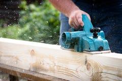 Chiuda sulle mani del carpentiere che funzionano con la piallatrice elettrica sulla plancia di legno immagini stock