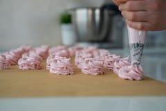 Chiuda sulle mani del cuoco unico con la crema della borsa della confetteria alla carta pergamena alla cucina del negozio di past fotografia stock