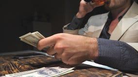Chiuda sulle mani del trafficante di droga che tengono i contanti e che contano la valuta estera sopra la tavola Le armi maschii  video d archivio