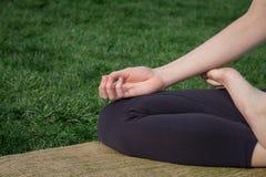 Chiuda sulle mani dell'immagine di meditare la donna su erba verde Fotografia Stock Libera da Diritti