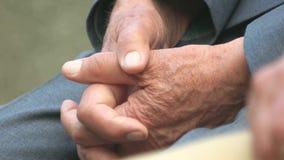 Chiuda sulle mani dell'uomo anziano stock footage