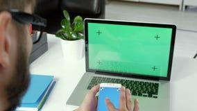 Chiuda sulle mani dell'uomo che tengono lo Smart Phone con lo schermo verde Primo piano Chiuda sulle mani del maschio che fanno s archivi video