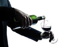 Chiuda sulle mani dell'uomo che versano il vino rosso in un vetro Fotografia Stock Libera da Diritti