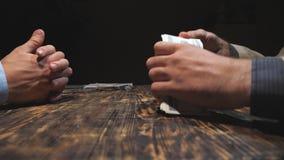 Chiuda sulle mani dell'uomo d'affari che mettono un pacco di valuta estera sulla tavola Armi maschii del trafficante di droga che archivi video