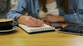 Chiuda sulle mani della donna che tengono lo smartphone e che scrivono con una matita in taccuino nel caffè archivi video