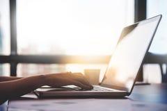 Chiuda sulle mani della donna facendo uso del computer portatile per il suo lavoro Immagine Stock Libera da Diritti