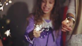 Chiuda sulle mani della famiglia con le luci delle stelle filante nella notte di Natale archivi video