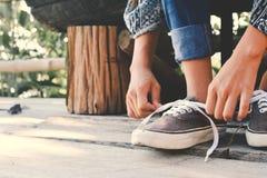 Chiuda sulle mani della ragazza che legano il laccetto sulle scarpe Immagini Stock Libere da Diritti