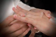 Chiuda sulle mani della sposa e dello sposo che mettono sull'le fedi nuziali Immagine Stock