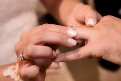 Chiuda sulle mani della sposa e dello sposo che mettono sull'le fedi nuziali Fotografia Stock