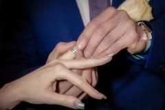 Chiuda sulle mani della sposa e dello sposo che mettono sull'le fedi nuziali Fotografie Stock Libere da Diritti
