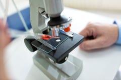Chiuda sulle mani dello scienziato con il microscopio Fotografie Stock Libere da Diritti