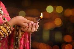 Chiuda sulle mani indiane della donna che tengono la luce di diya immagine stock libera da diritti