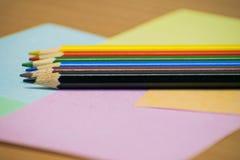 Chiuda sulle matite di colore della pila su papper e su fondo di legno fotografie stock libere da diritti