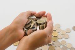 Chiuda sulle monete in mani sul fondo bianco della tavola Soldi di risparmio fotografia stock libera da diritti