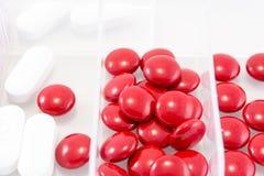Chiuda sulle pillole rosse e bianche in scatola Immagine Stock