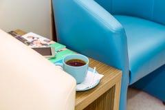 Chiuda sulle sedie dell'avorio e blu e su una tazza di caffè sulla tavola a sala di attesa, corridoio Fuoco selettivo Immagini Stock