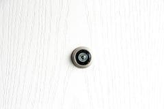 Chiuda sullo spioncino della lente della porta su struttura di legno bianca Fotografia Stock Libera da Diritti