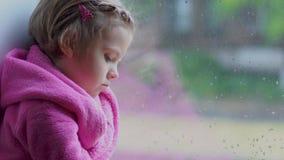 Chiuda tristemente su di piccola ragazza sveglia negli sguardi fissi rosa dell'accappatoio da una finestra Sedendosi sul davanzal video d archivio