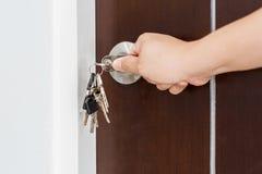 Chiudendo o sbloccando porta a chiave con la chiave a mano immagine stock libera da diritti