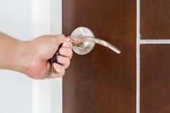 Chiudendo o sbloccando porta a chiave con la chiave a mano Immagine Stock