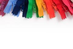 Chiusure lampo variopinte nei colori differenti su fondo bianco Fotografia Stock