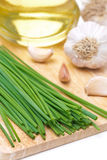 Chives, garlic and olive oil on a wooden board Stock Photo
