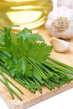 Chives, parsley, garlic and olive oil on a wooden board Royalty Free Stock Photo